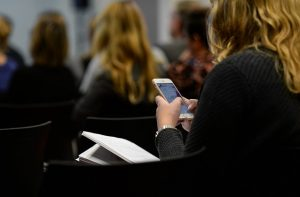 girl using an app at a conference, instead of wasteful printed materials